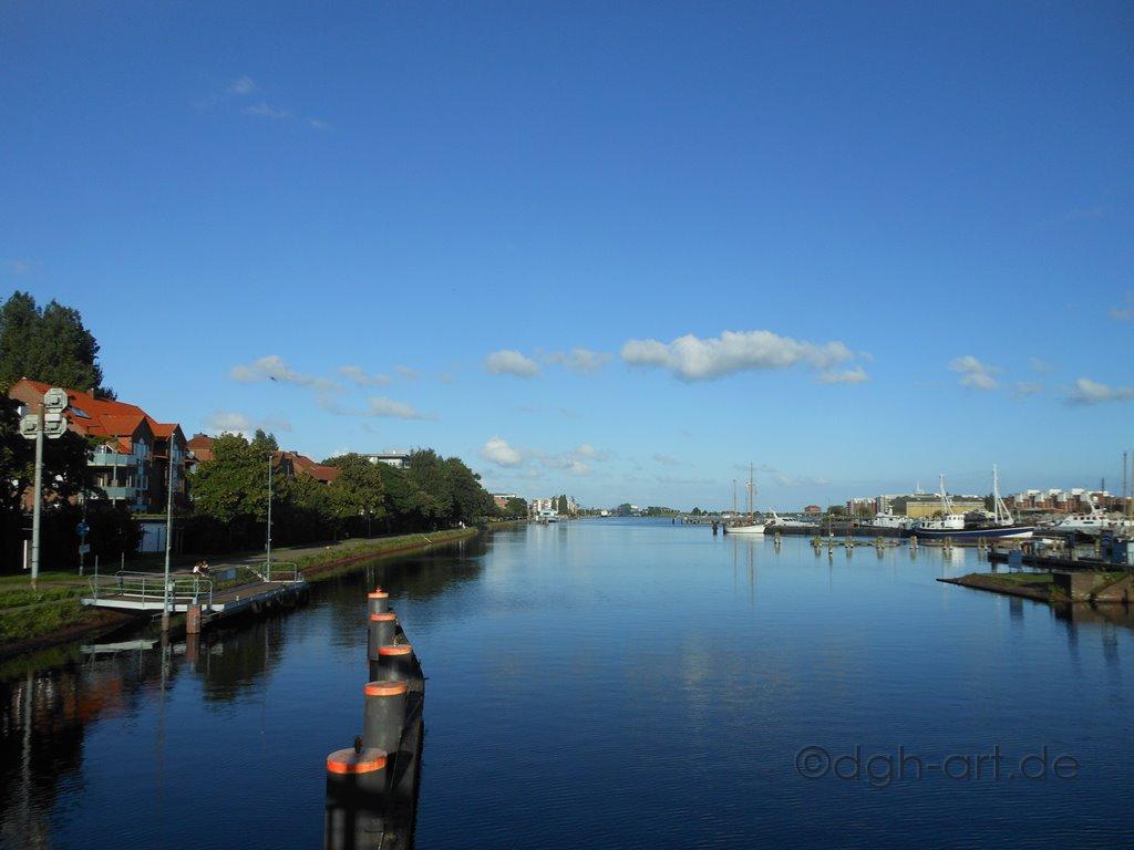 Blaue Stimmung durch Himmel und Wasser. Bildszenerie am Ems-Jade-Kanal von der Deichbrücke in Wilhelmshaven gesehen.