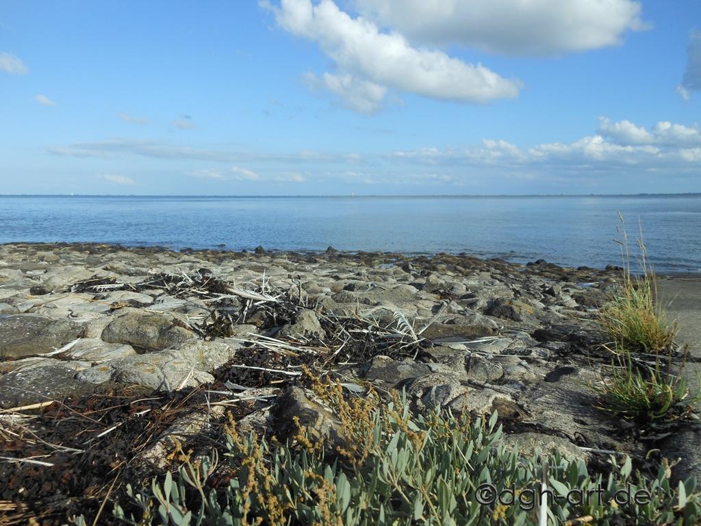Befestigter Steinstrand am Deich von Wilhelmshaven, am Rande des Nationalpark Wattenmeer. Der Südstrand in Wilhelmshaven und der Meereseinschnitt Jadebusen.
